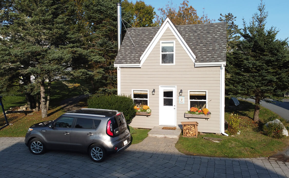 Exterior shot of a cottage at Oceanstone with parking out front